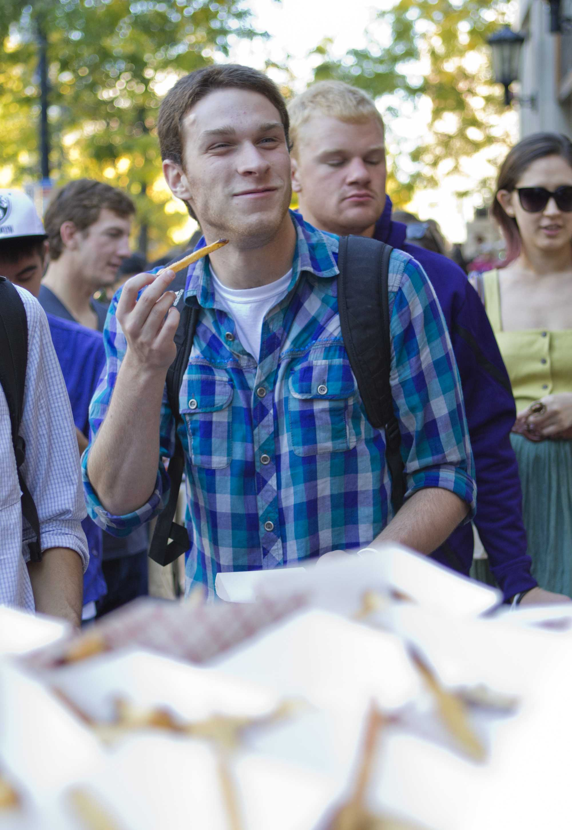 Communication junior Scott Wolf eats truffle fries from Edzo's Burger Shop in downtown Evanston during Sunday's Big Bite Night. This year, over 30 different restaurants participated in the annual event.