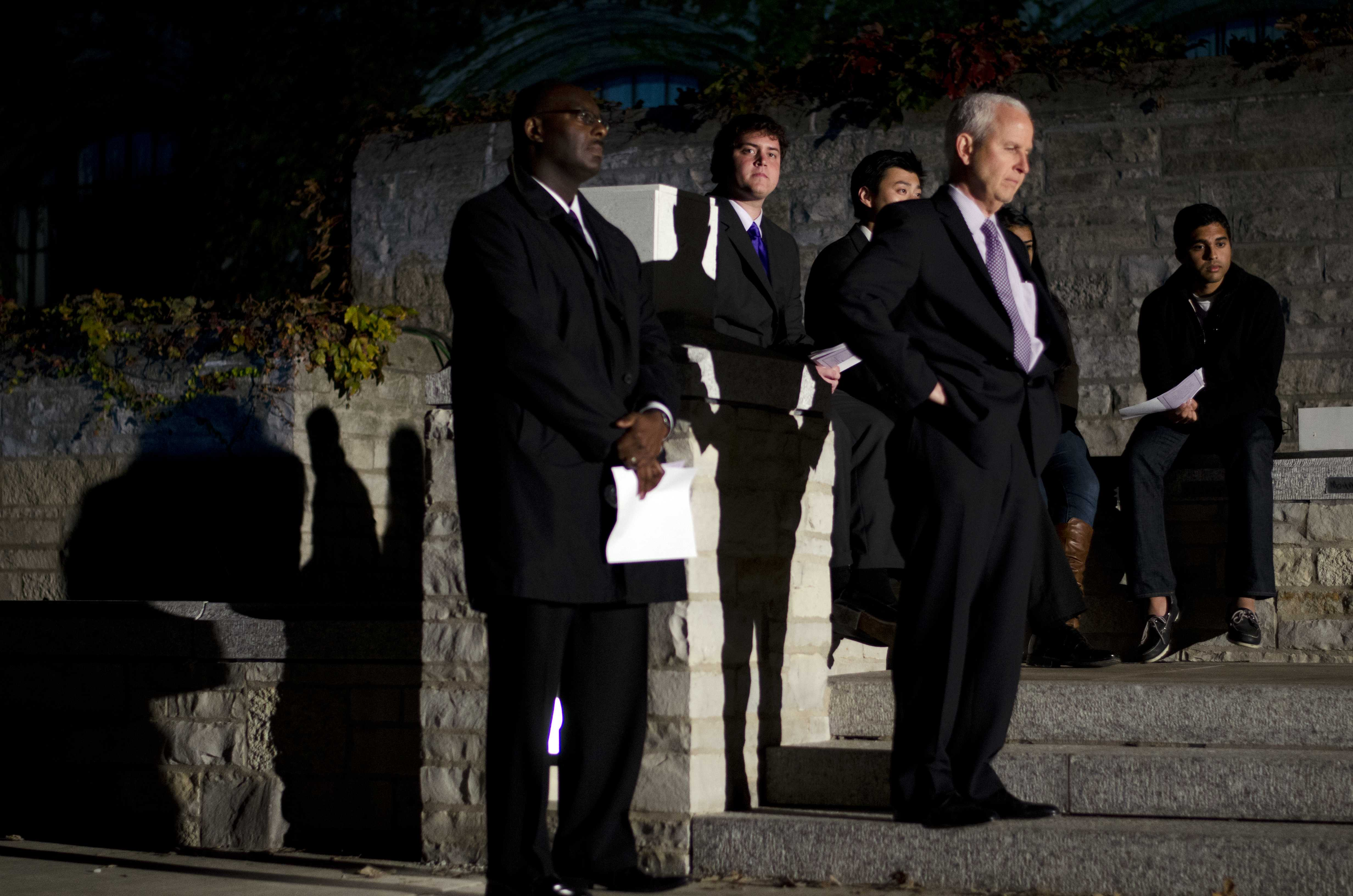Burgwell Howard, assistant vice president for student engagement, and University President Morton Schapiro (left to right in the foreground) watch on as student commemorate Harsha Maddula, the missing student whose body was found in Lake Michigan on Thursday evening.