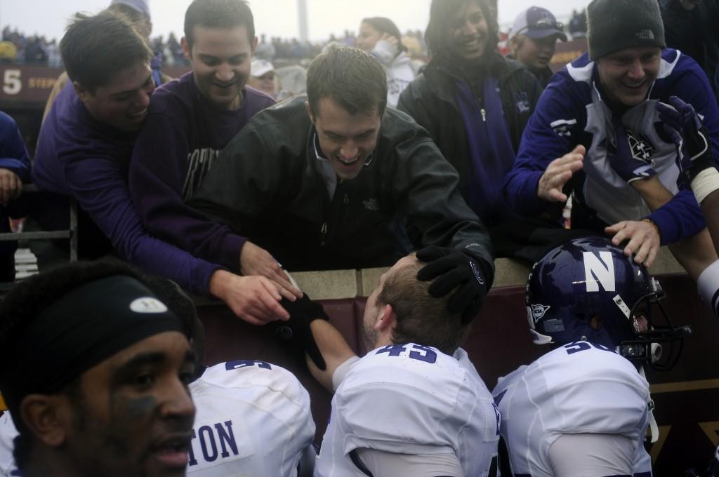 Northwestern linebacker Colin Ellis celebrates with fans who stuck through the rain at TCF Bank Stadium in Minneapolis.