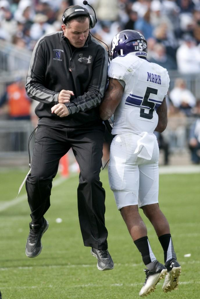 Coach Pat Fitzgerald celebrates with junior Venric Mark after the running back's 75-yard punt return touchdown.