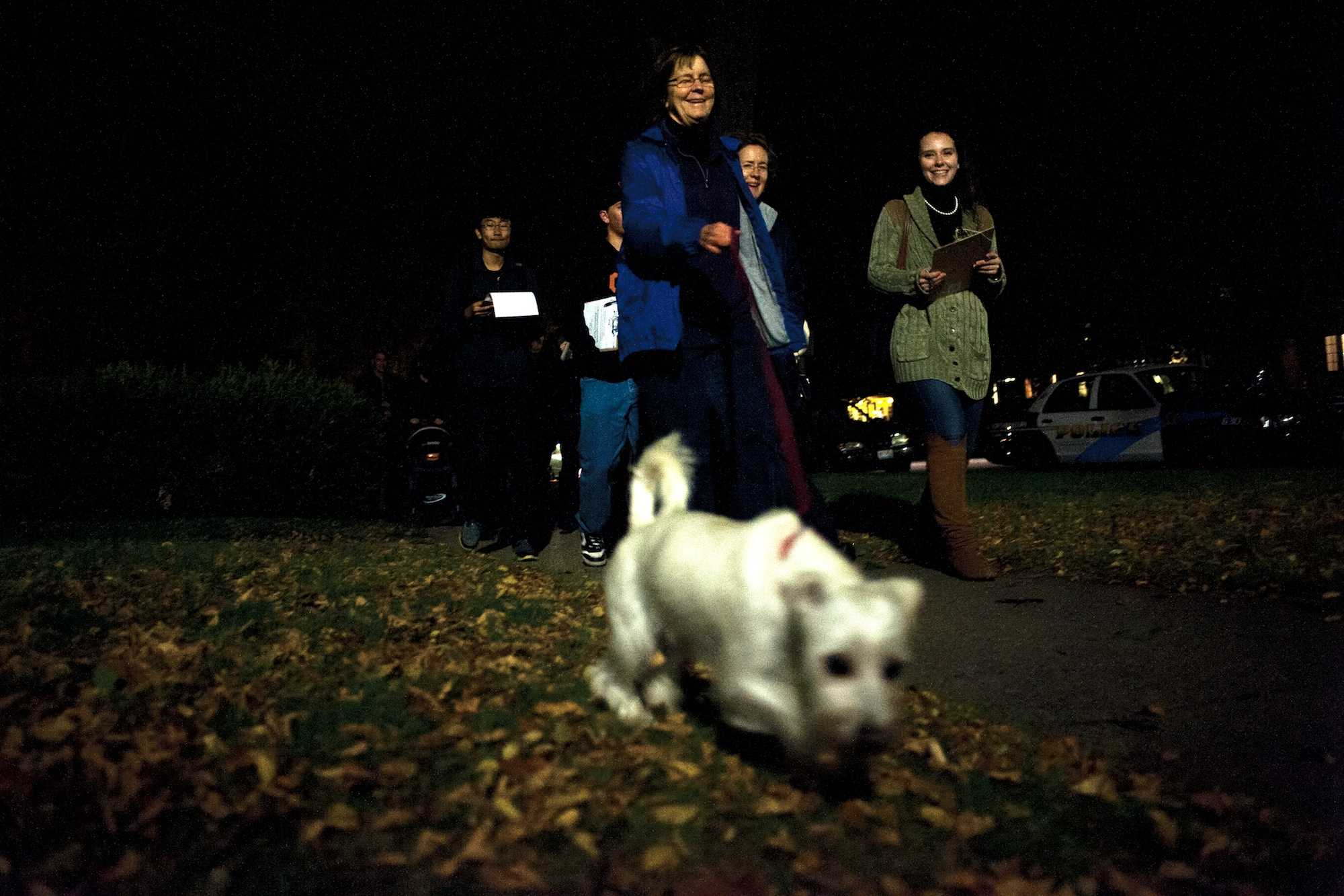 Evanston Mayor Elizabeth Tisdahl (center) tugs on her dog Comet's leash while participating in a walk organized by Associated Student Government senator Jane Gilmore (right) to identify poorly lit off-campus areas.