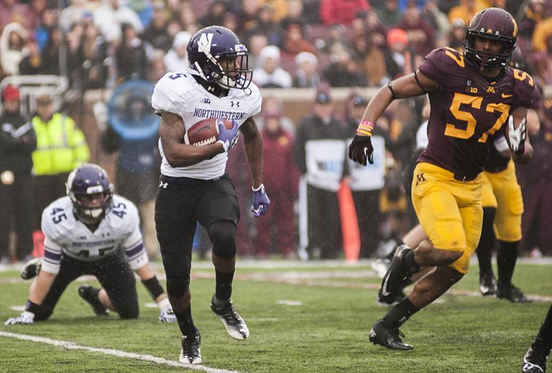 Northwestern running back Venric Mark evades tacklers on the wet field at Minnesota. Mark provided the majority of the offense for the now-bowl eligible Wildcats, rushing for a career high 182 yards on 20 carries.