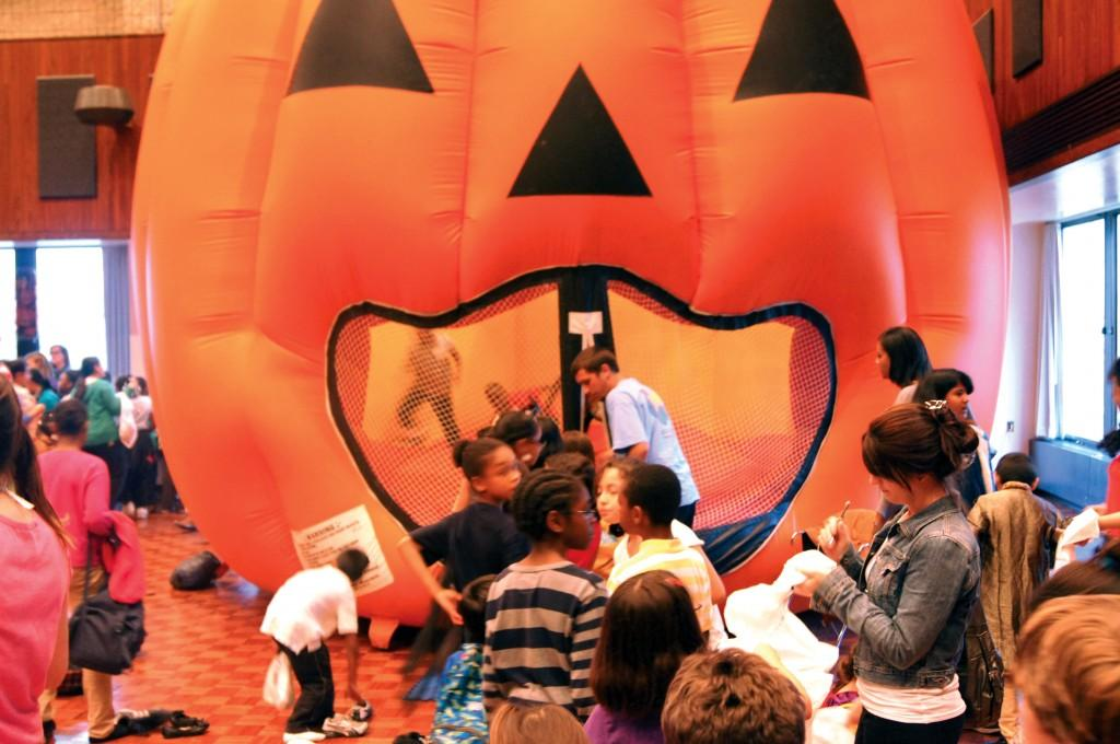 Children line up for a Halloween-themed moon bounce at Northwestern's Project Pumpkin at the Norris University Center on Thursday.