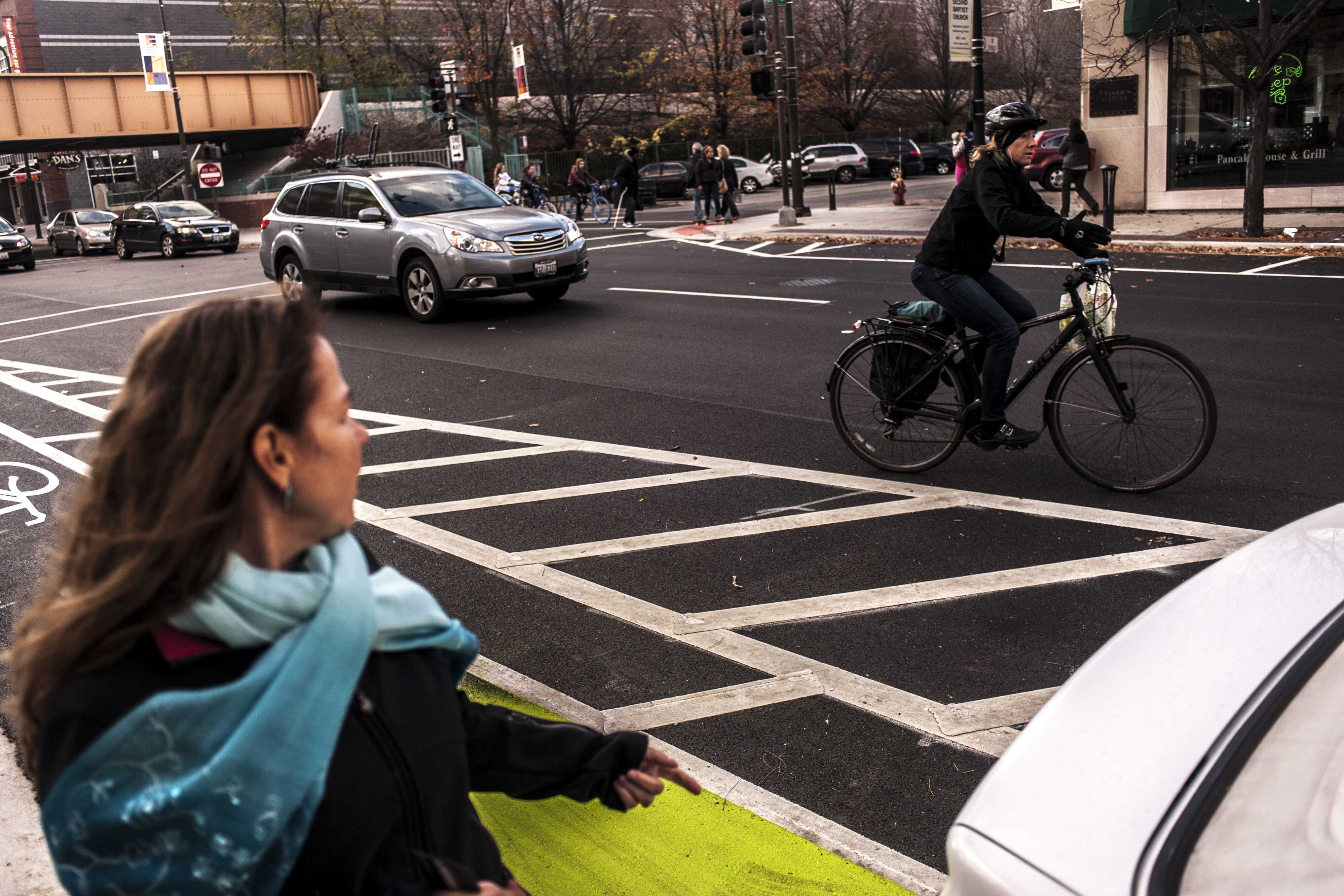 Evanston resident Nancy Floy (left) watches a cyclist veer into traffic to avoid hitting Floy's car, which was parked in a bike lane Sunday. Floy complained that the new lane made it harder for her to park illegally and said she worried that doors of cars parked legally would pose a danger to cyclists.