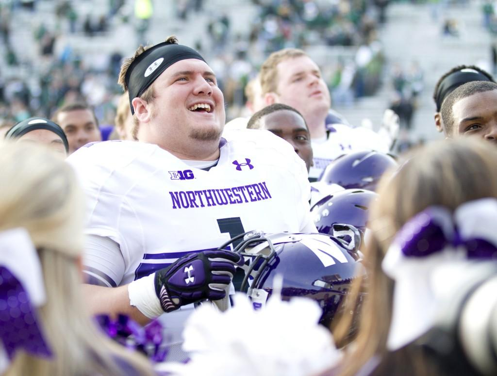 Northwestern defensive lineman Bo Cisek (1) sings the Northwestern fight song with fans after the Wildcats' 23-20 win over Michigan State on Saturday. The Cats' have now improved their record to 8-3.