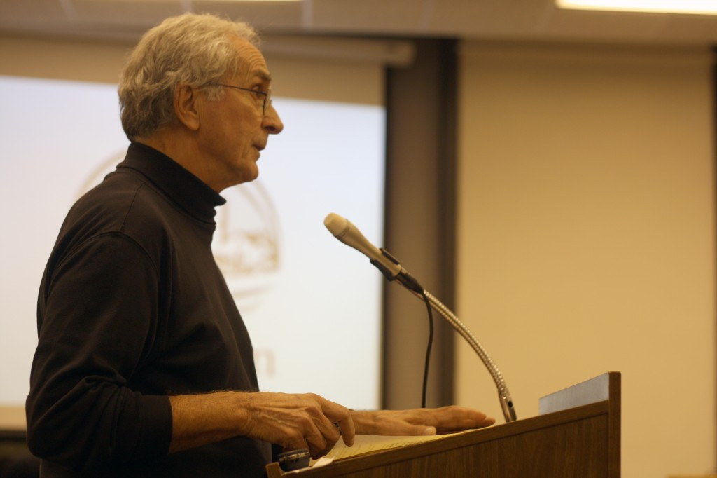 Jack Weiss of the Evanston Preservation Commission approaches the Evanston City Council to voice concerns about the appearance of Northwestern's planned visitors center. He was one of many residents who spoke critically of NU during Monday's meeting.