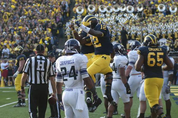 Northwestern defensive back Ibraheim Campbell (24) watches as Michigan quarterback Devin Gardner (12) celebrates after rushing into the end zone for a touchdown that took Saturday's game into overtime.
