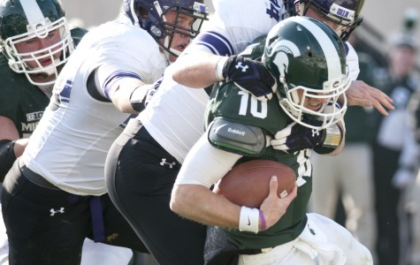 Northwestern defensive lineman Dean Lowry (94) brings down Michigan State quarterback Andrew Maxwell at the Spartans' three-yard line. It was the only sack of the half for the Wildcats.