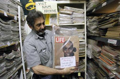 Bob Katzman pulls out an issue of Life magazine in his store Magazine Museum. Katzman sells antique periodicals, posters and newspaper front pages.