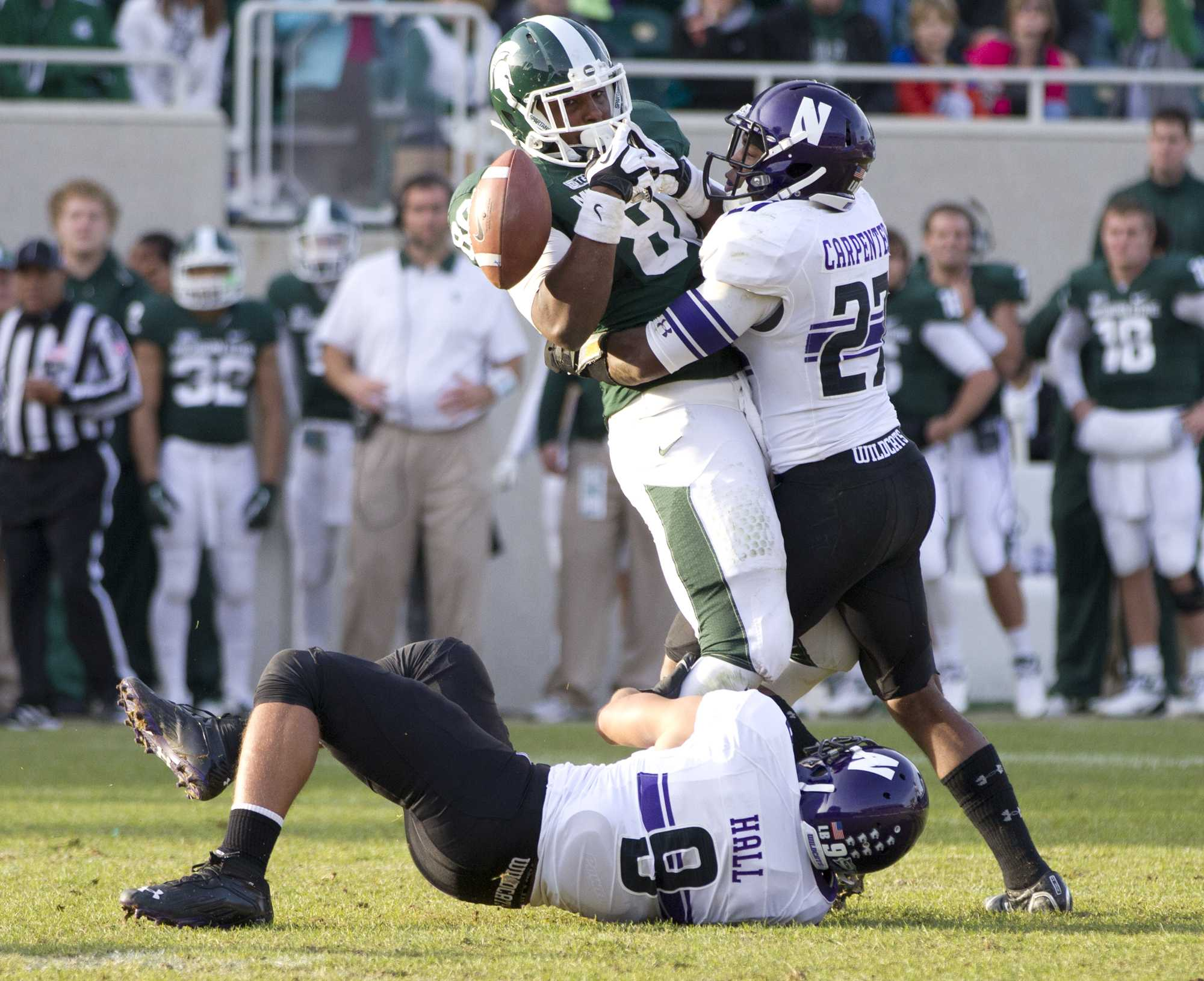Northwestern safety Jared Carpenter (27) breaks up Michigan State's fourth-down pass at the end of the game. With the incompletion, the Wildcats sealed their 23-20 win.