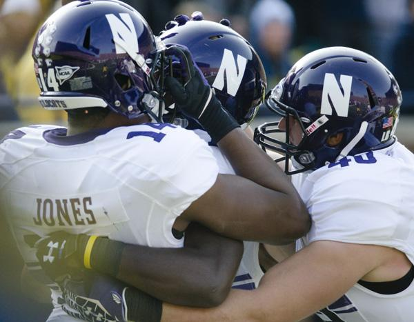 Northwestern wide receiver Cameron Dickerson celebrates with teammates after catching the first touchdown pass of his career. The touchdown brought NU into a 14-14 tie with Michigan going into halftime.