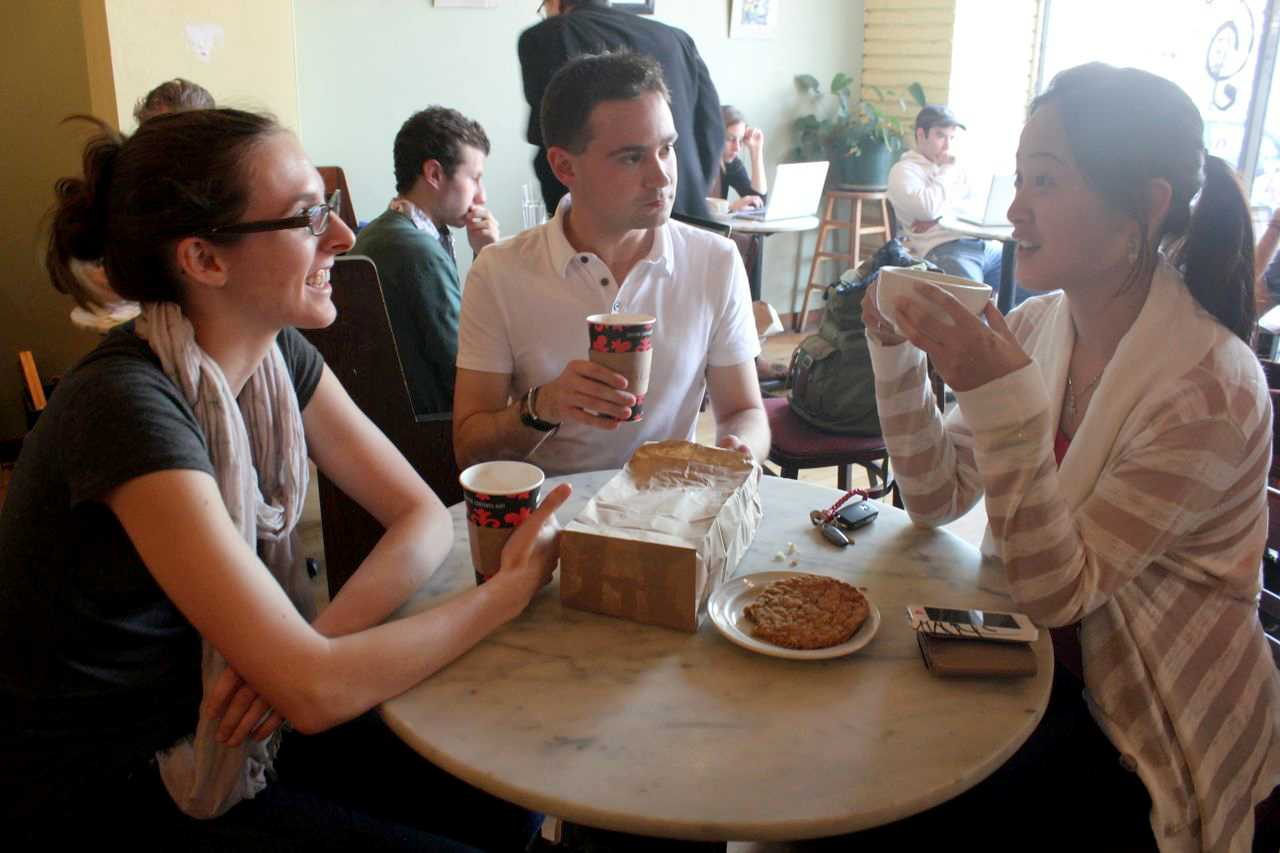 Northwestern graduate students Amy Hess, Chris Ramaekers and Yuchi Chou chat over coffee and dessert at the Unicorn Cafe.