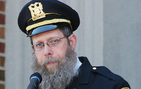 Rabbi Hillel Klein, wearing his uniform as an chaplain of the Evanston Police Department, speaks at an event. Klein has been at the center of an ongoing controversy regarding Northwestern's disaffiliation with the Chabad House.