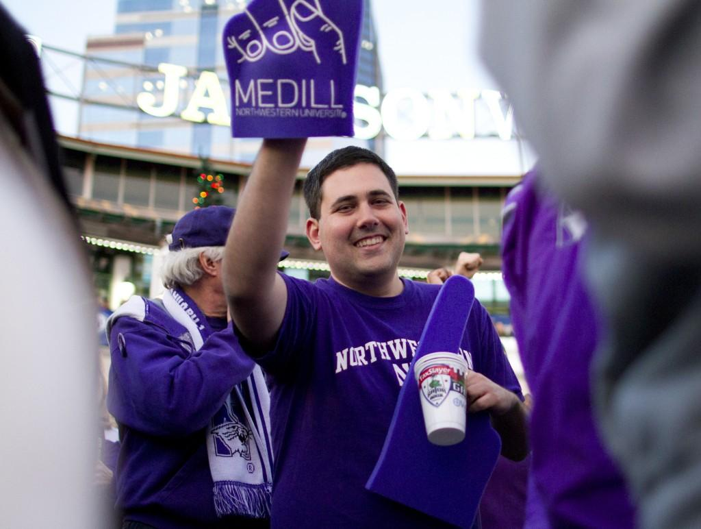 A Northwestern fan shows off his foam finger during the Wildcats' pep rally in Jacksonville Monday night before the Gator Bowl.