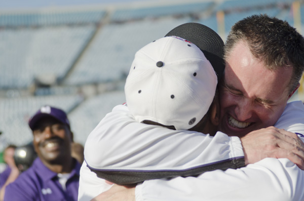Coach Pat Fitzgerald hugs an assistant coach on the sidelines at the end of Northwestern's 34-20 win over Mississippi State in the 2013 Gator Bowl.