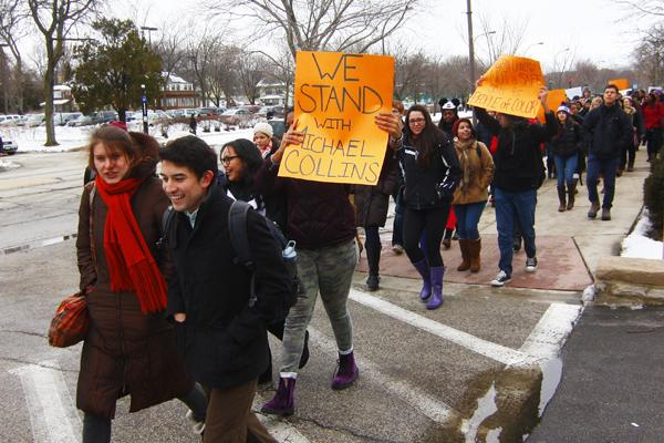 One+student+holds+a+sign+expressing+solidarity+with+Michael+Collins+as+they+walk+down+Sheridan+Road+during+Thursday%27s+march.