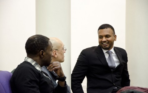 Zaheer Ali, who was part of the Malcolm X project at Columbia University, speaks with (from left) Loyola Prof. Kim Searcy and Evanston resident Eric Basir.