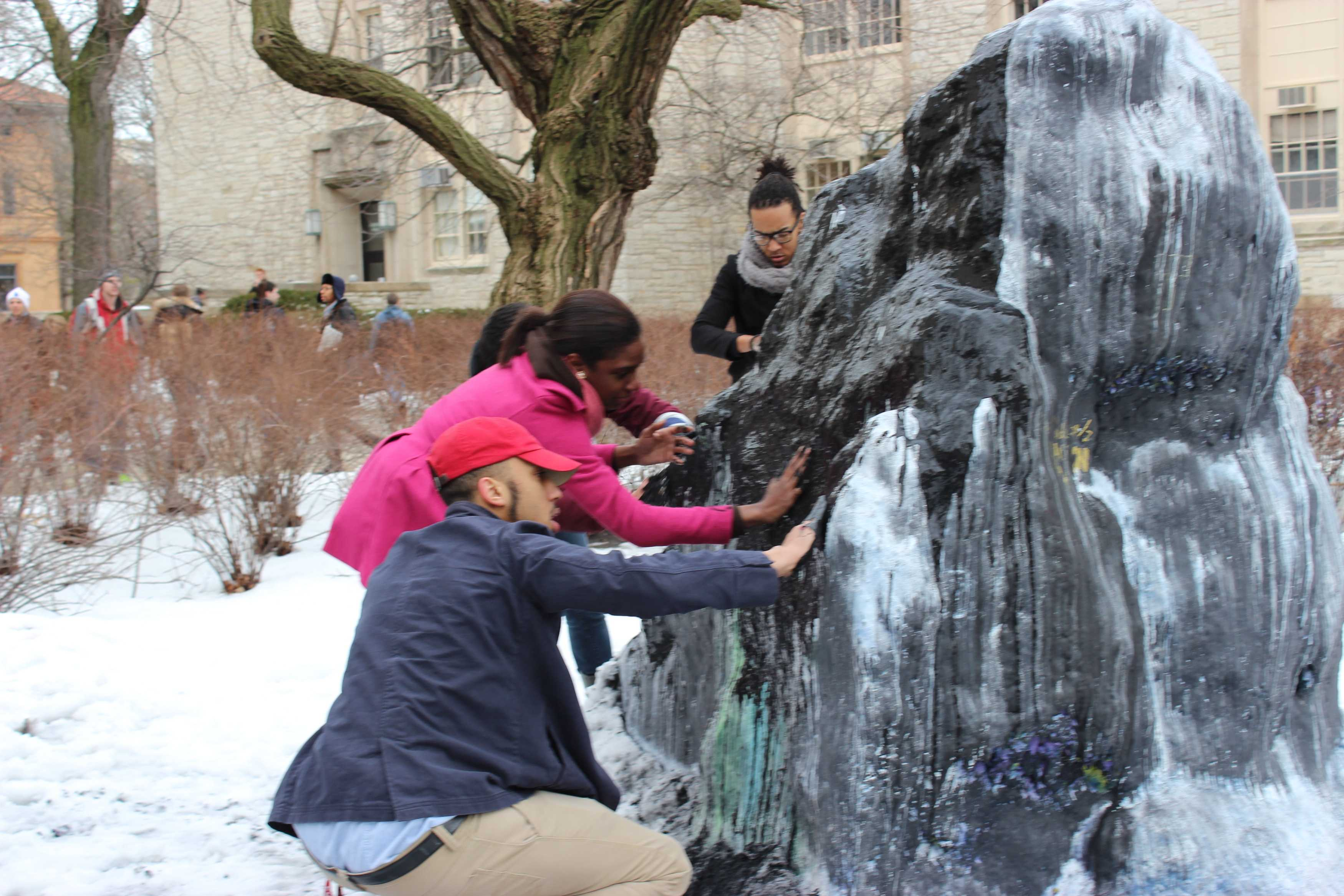 Students cover The Rock in black paint to symbolize Northwestern is a
