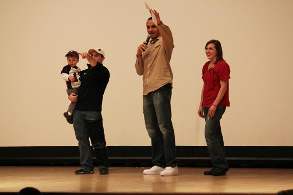 Host and senior basketball player Reggie Hearn (center), senior wrestler Levi Mele (left) and his family look for Mele's second child during his comedy routine. The student athlete talent show, which featured ten acts, raised money for Dance Marathon.