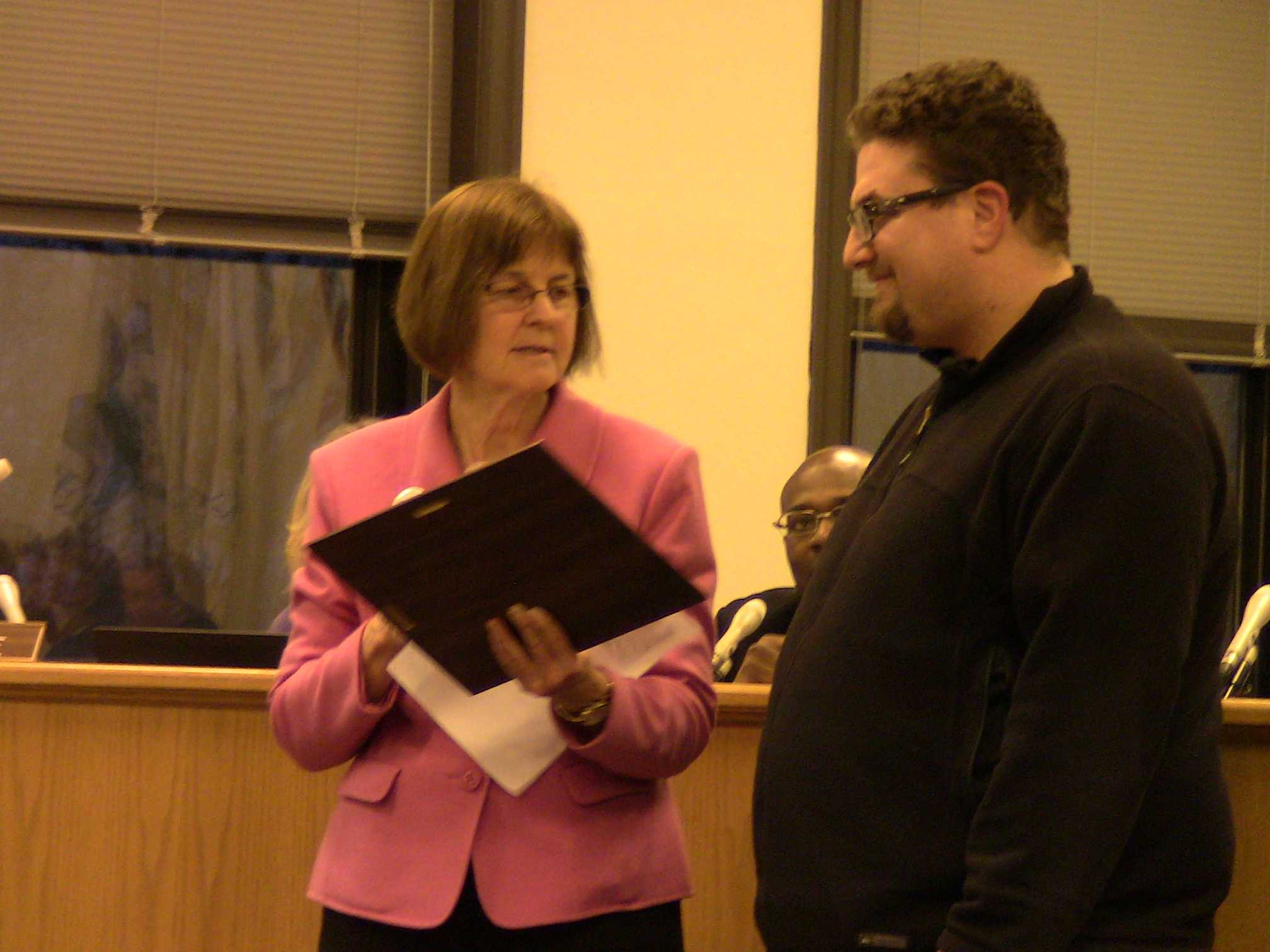 "Mayor Elizabeth Tisdahl presents an award to Edzos Burger Shop chef Eddie Lakin for serving one of the top 25 burgers in the U.S. ""Simply awesome top of the line burgers with tons of options for customization plus a  fantastic selection of to die for fries,"" Tisdahl reads from the award given by restaurant guidebook publisher Zagat."