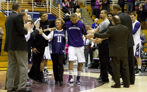 Senior guard Reggie Hearn high fives teammates as he walks onto the court with his mother during Senior Night at Welsh-Ryan Arena.