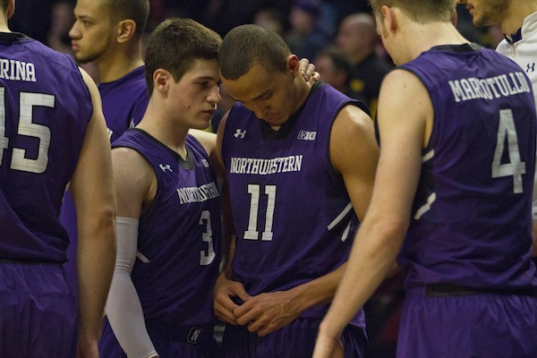 Sophomore guard Dave Sobolewski (left) consoles senior guard Reggie Hearn (11) after Hearn's Northwestern career ended with a 73-59 loss to Iowa on Thursday night.