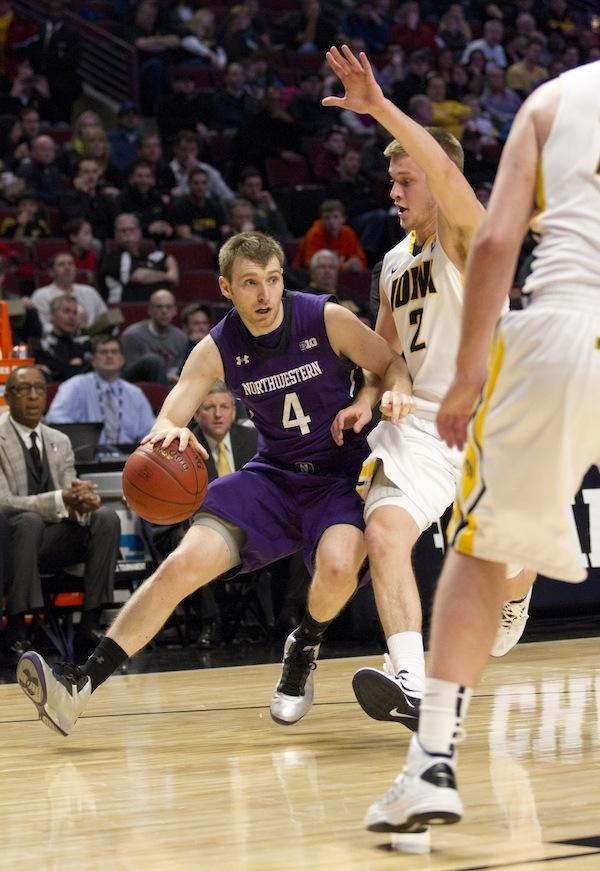 Senior guard Alex Marcotullio tries to dribble past Iowa guard Josh Oglesby during Thursday's Big Ten Tournament match.