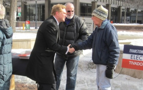 1st Ward challenger Edward Tivador speaks with a supporter at a campaign event earlier this month. Tivador's campaign announced endorsements Friday from former Evanston mayors Jay Lytle and Lorraine Morton.