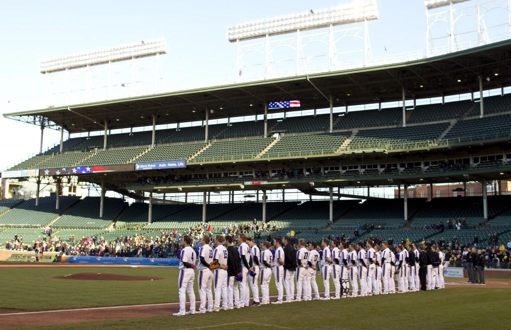 The Northwestern baseball team looks across Wrigley Field as the National Anthem plays before the start of Saturday's game against Michigan.