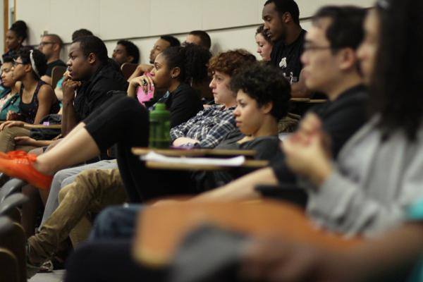 Students listen intently to an audio media presentation concerning community within the Northwestern study body.