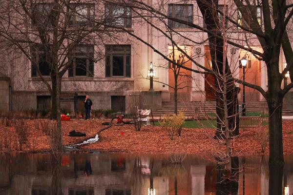 A Northwestern maintenance worker drains the puddle in front of Swift Hall. Thursday's heavy rains flooded multiple facilities and residences on campus.