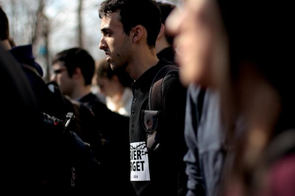 """A Northwestern student wearing his """"Never Forget"""" sign on his shirt listens to the Rabbi's speech to the students."""