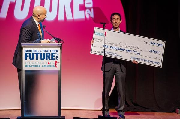McCormick senior Dennis Ai accepts prize money on behalf of JiveHealth in Washington, D.C. The technology start-up placed first in the Partnership for a Healthier America End Childhood Obesity Innovation Challenge hosted by First Lady Michele Obama.