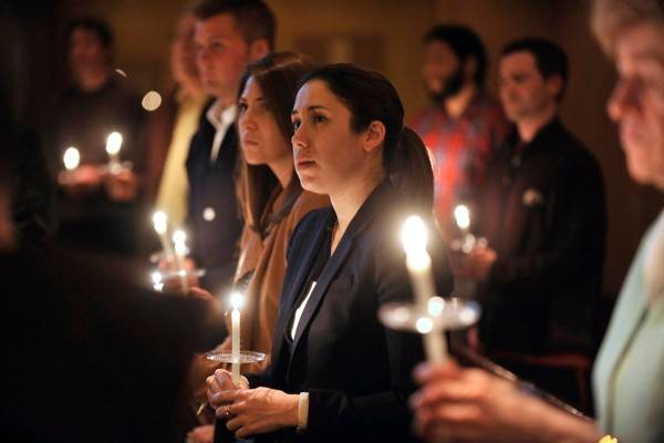 People pray during an interfaith candlelight service at the Paulist Center Boston on Tuesday. The city is in mourning today for three killed and at least 144 wounded in the bombing at the Boston Marathon.