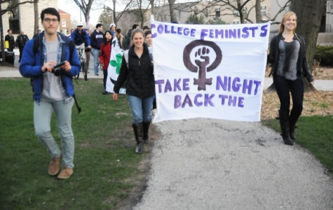 Weinberg sophomores Erin Quick (left) and Linzy Wagner (right) hold the banner during the Take Back the Night rally on Thursday. The event was held by College Feminists, Sexual Health and Assault Peer Educators, and Men Against Rape and Sexual Assault.