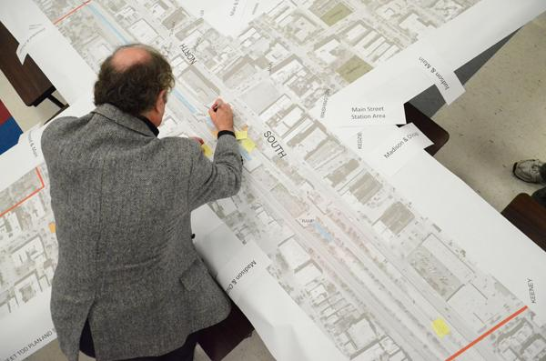 John Szostek writes suggestions for improvement of the Main Street Metra Station on a large map at a workshop hosted by the city Thursday. Szostek leases the land where the station is located, and he said he wants to see more people on the street corner.