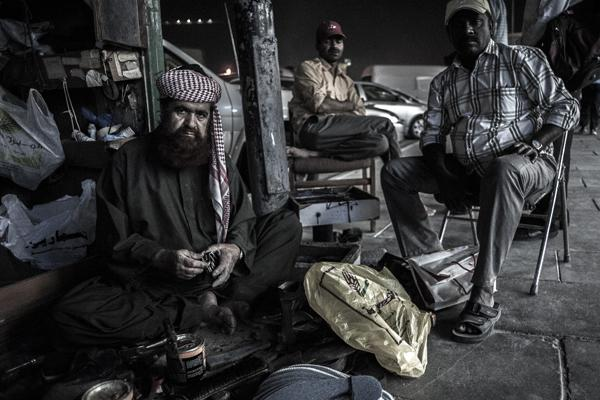 A cobbler and his clients sit on the sidewalk in the Msheireb neighborhood in Doha, the location of NU-Q's enterprise reporting classes.