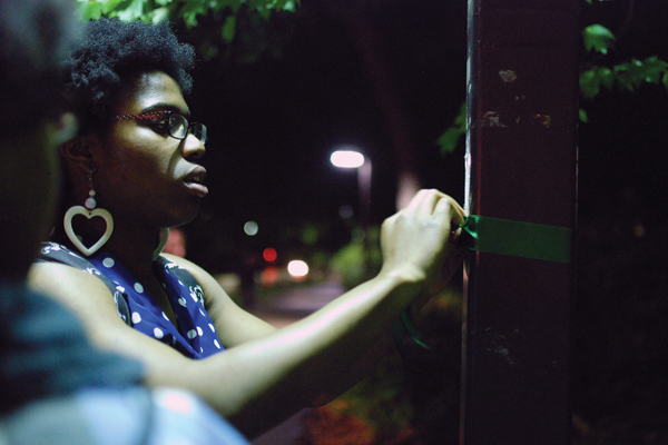 SESP junior Rebecca Abara ties a ribbon to a lamp post on Sheridan Road late Thursday night to commemorate the end of Mental Health Awareness Month. The event was forced to end early due to the rain.