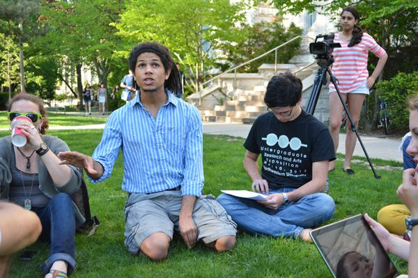 Weinberg senior Noah Charles speaks Tuesday afternoon at the People's Gathering on the lawn by The Rock. Spearheaded by about 20 students, the event aimed to demonstrate the use of public space for positive change.