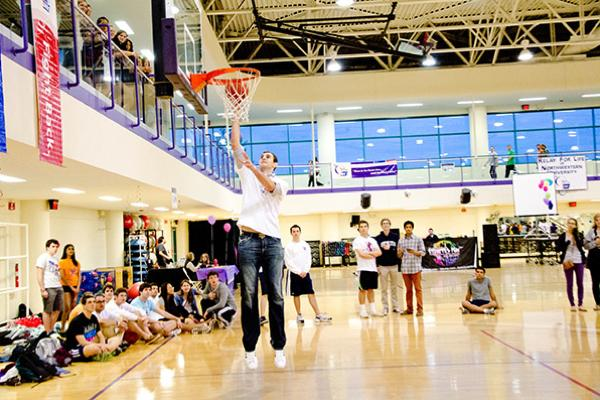 Men's basketball center Alex Olah makes a lay-up on Friday evening at the annual Relay for Life event at SPAC. The men's basketball team was present to support a knockout competition held for Relay participants.