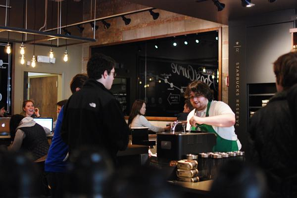 A Starbucks employee prepares an order for customers Sunday afternoon at the coffee shop's new location on Sherman Avenue. The new location, which is larger than the old one, had its grand re-opening Friday evening.