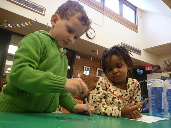 Ian Torrisi (left) and Ayah Sol Hall (right) participate in National Drinking Water Week by demonstrating water tension in an after-school activity. The event was held Monday at the Evanston Ecology Center, 2024 McCormick Blvd.