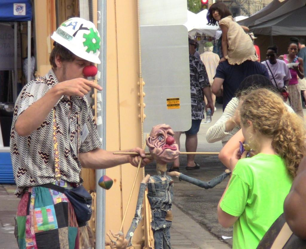 A+street+performer+plays+with+a+puppet+Sunday+at+Custer%27s+Last+Stand%2C+an+annual+arts+festival+near+Main+Street.+The+weekend+fair+got+off+to+a+slow+start+due+to+rain+and+strong+winds+Saturday.+