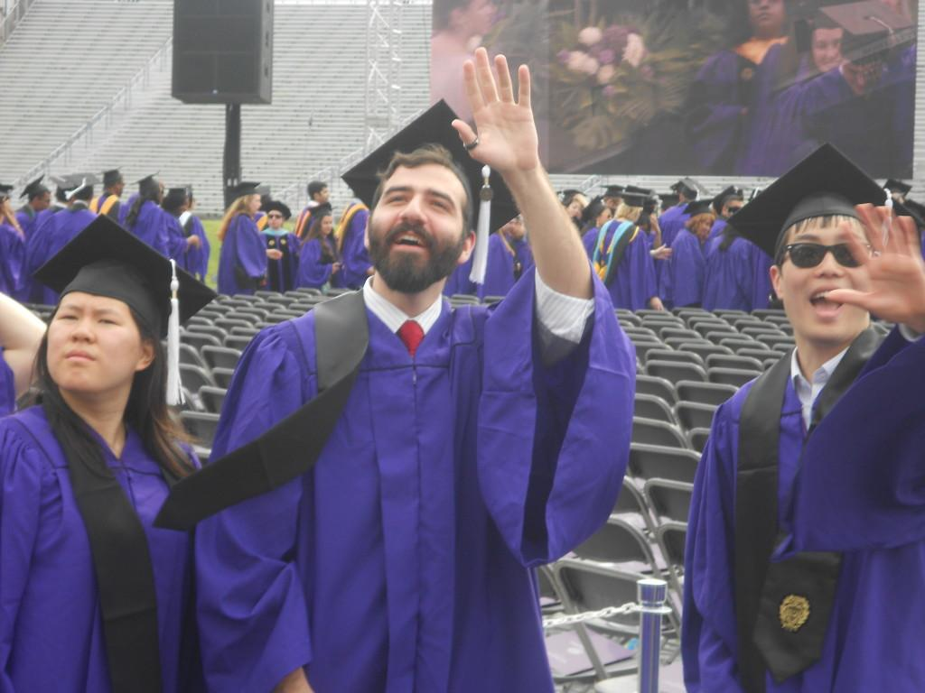 Graduating+seniors+wave+to+their+family+members+as+they+walk+onto+Ryan+Field+on+Friday+morning.+More+than+12%2C000+people+attended+Northwesterns+155th+commencement+ceremony%2C+according+to+University+officials.