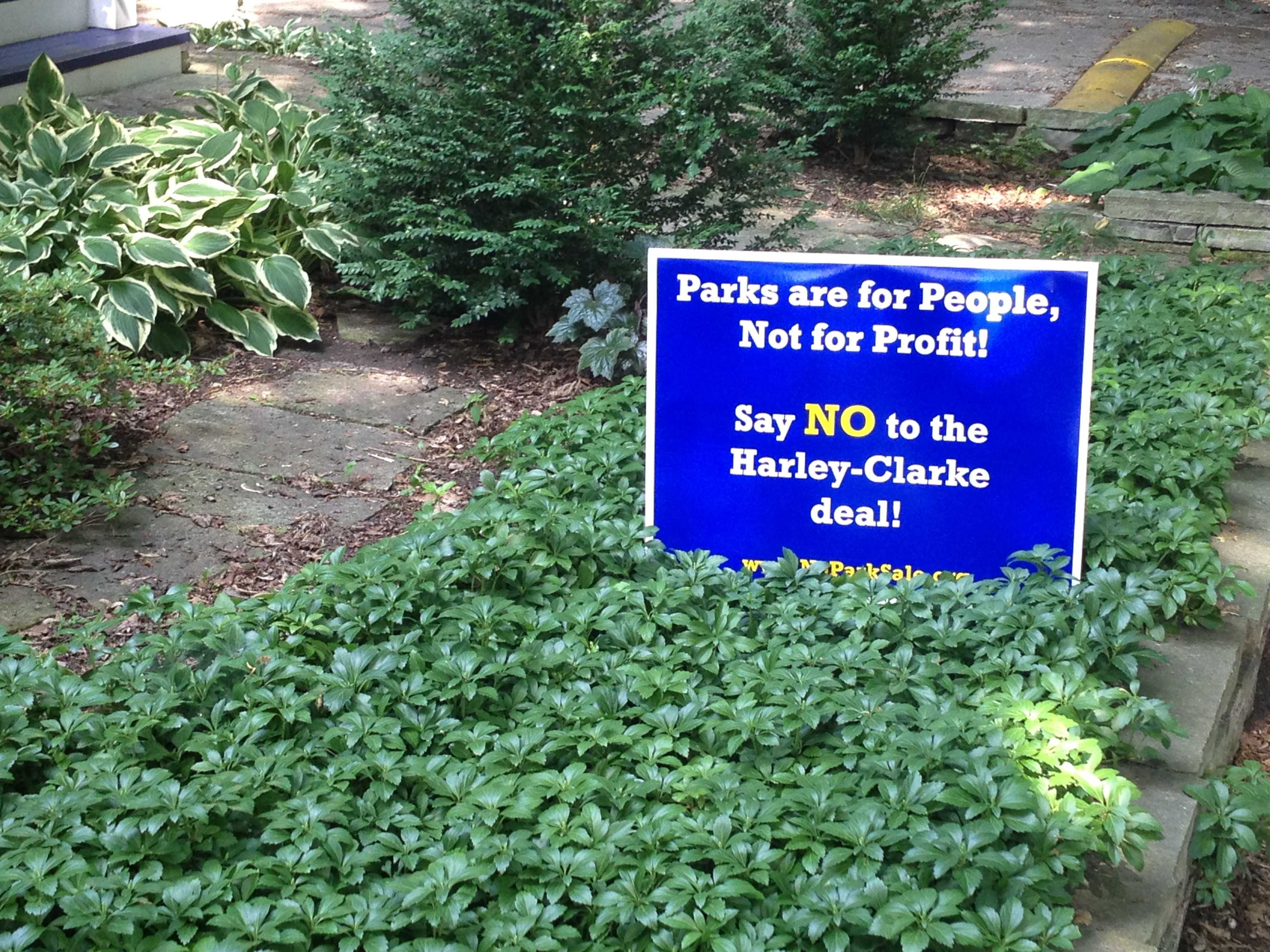 Several yard signs against the possible sale of the Harley Clarke Mansion have been planted along Central Street. The city says it can no longer afford to maintain the lakefront property.
