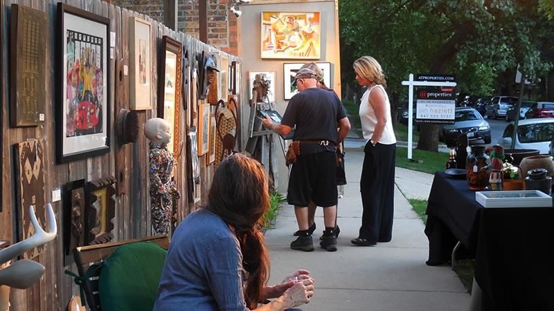 An+Evanston+artist+presents+his+work+to+potential+customers+Friday+evening+at+Art+Hop.+The+second+annual+showcase+gave+residents+free+access+to+galleries+and+other+displays.%0D%0A