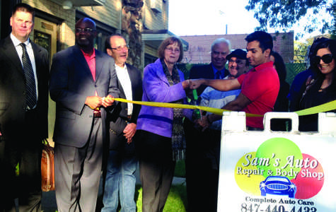 Evanston Mayor Elizabeth Tisdahl (center) helps cut the ribbon on Sam's Auto Repair & Body Shop, 2311 Main St. The business celebrated its official opening Wednesday evening.