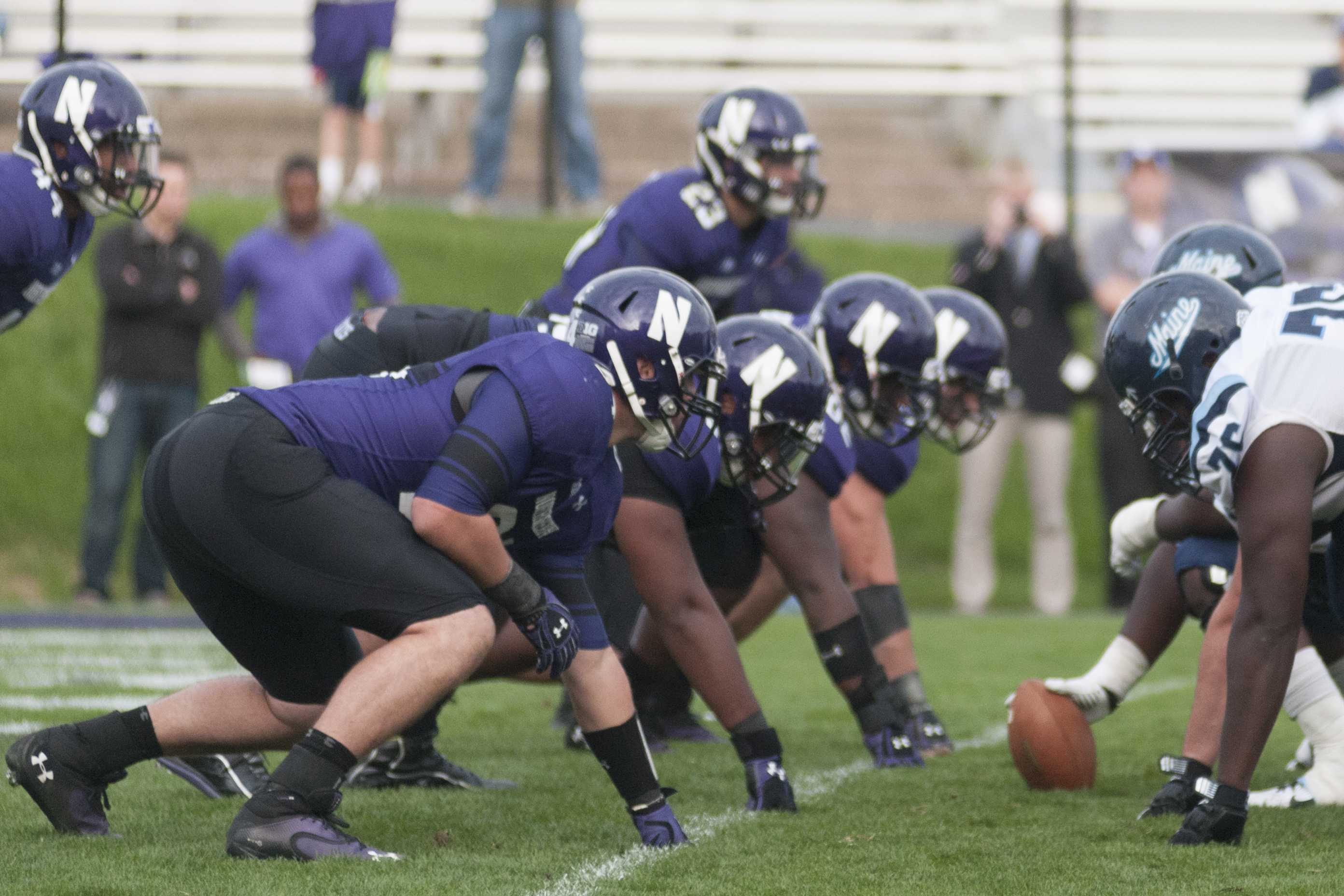 The Northwestern defensive line digs in during the team's game against Maine. The Wildcats' line will be key in slowing down Wisconsin's rushing attack Saturday.