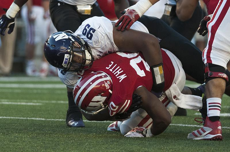 Defensive tackle Chance Carter brings down Wisconsin's James White in Saturday's game. The junior was named the Cats' defensive player of the week following the performance, in which he made six tackles. Monday, Carter had a front-row seat for NU's coaches' water balloon attack.