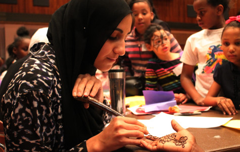 A Northwestern student gives a henna tattoo to a Project Pumpkin participant. The Muslim-cultural Student Association set up a booth at the event.